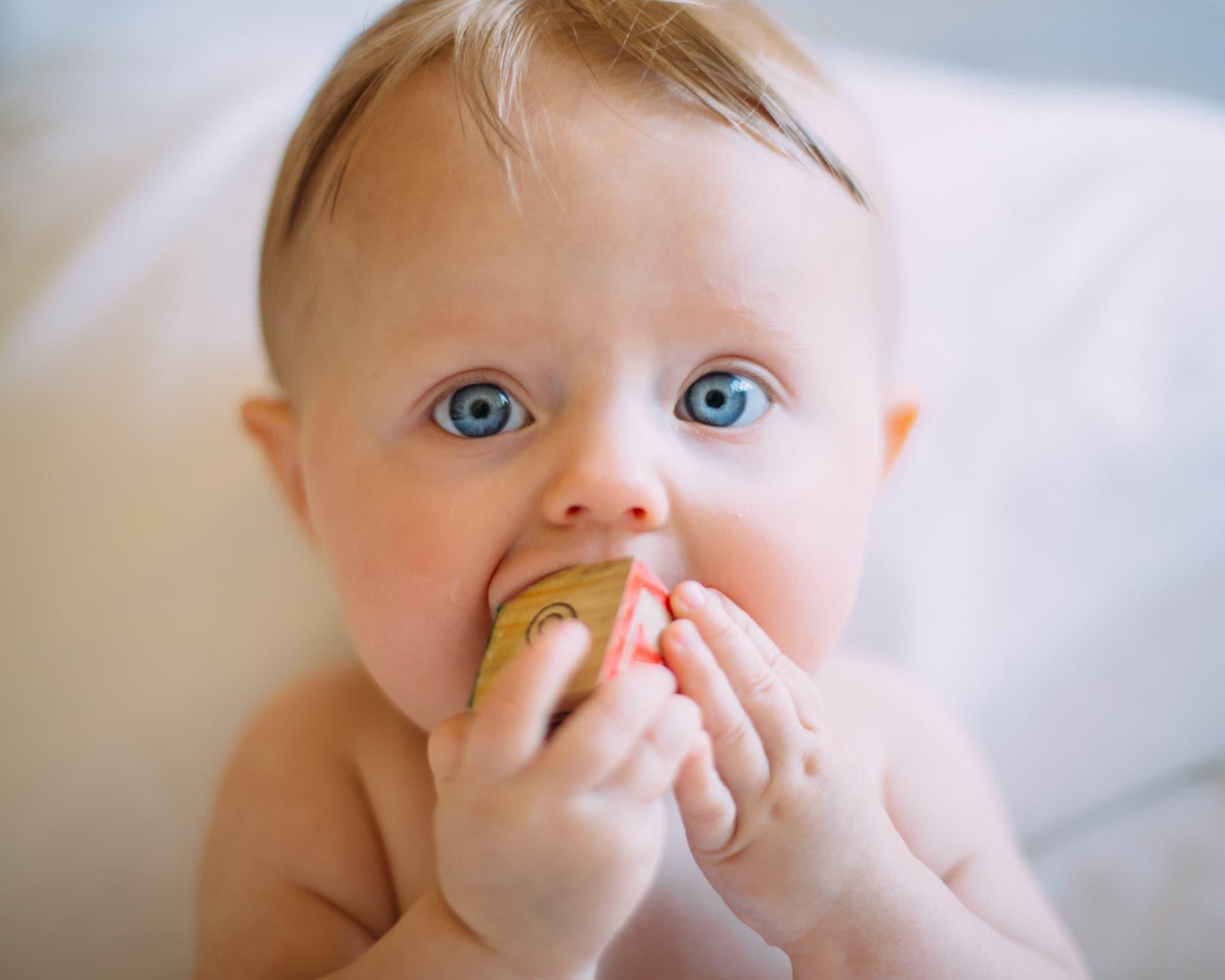 Bebé mordiendo una pieza de madera